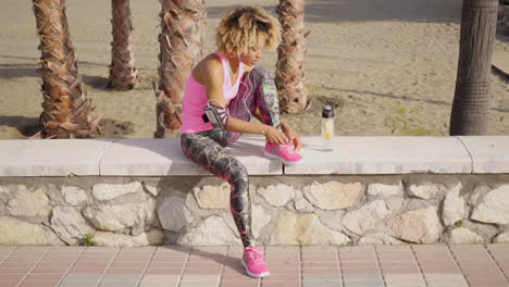 Seated-active-woman-tying-her-shoes-at-beach