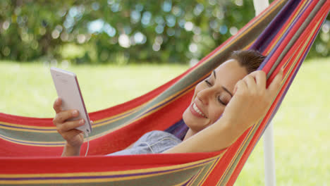 Happy-young-woman-listening-to-music-in-a-hammock