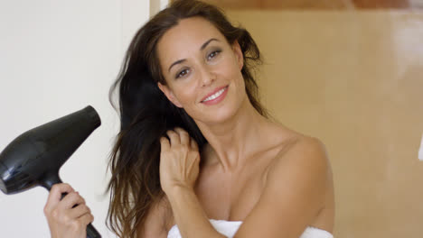 Gorgeous-young-woman-drying-her-long-hair