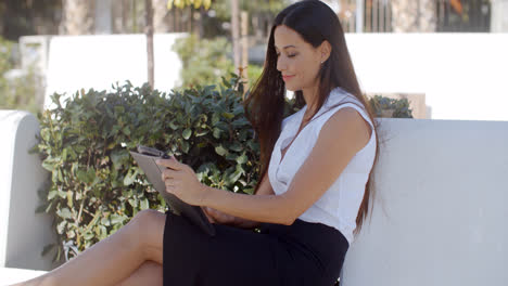 Smiling-young-woman-using-her-tablet-outdoors