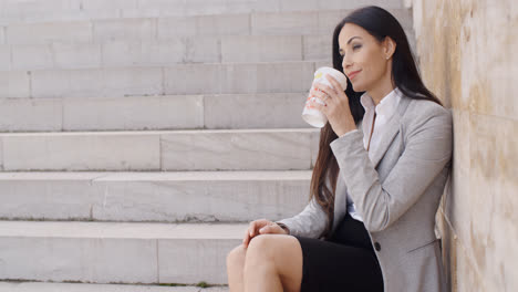 Grinning-woman-on-stairs-drinking-coffee