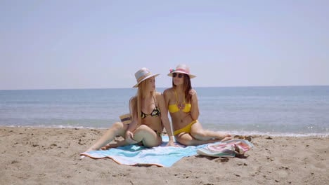 Two-sexy-young-women-sunbathing-on-a-beach