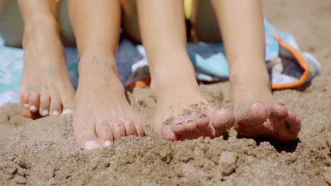 Bare-feet-of-two-young-women-in-beach-sand