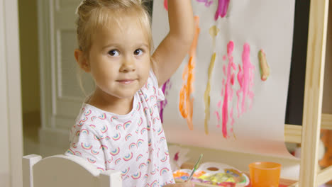 Pretty-confident-little-girl-painting-at-home