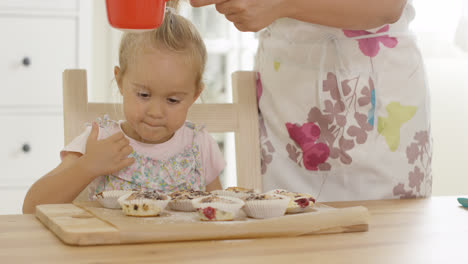 Girl-watching-sugar-fall-on-baked-muffins