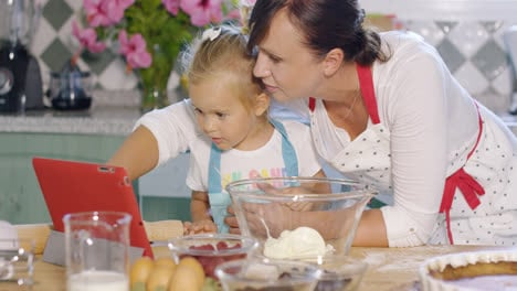 Mother-and-her-cute-young-daughter-in-the-kitchen