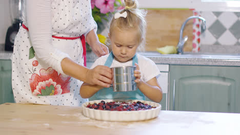 Mother-teaching-her-cute-little-daughter-to-bake