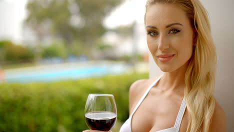 Woman-Holding-Glass-of-Red-Wine-Outdoors-near-Pool