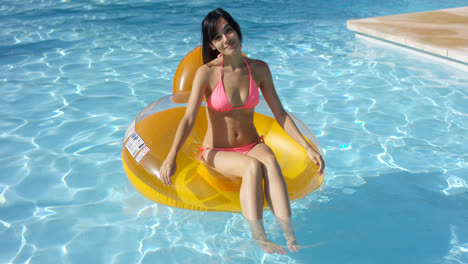 Lovely-young-woman-floating-in-a-swimming-pool