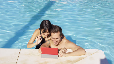 Smiling-couple-in-swimming-pool-use-digital-device