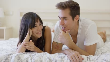Smiling-couple-talking-while-laying-down-on-bed