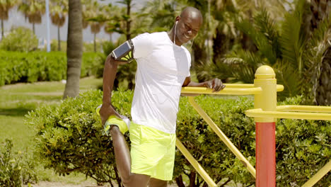 Bald-black-man-in-bright-green-shorts-and-ear-buds