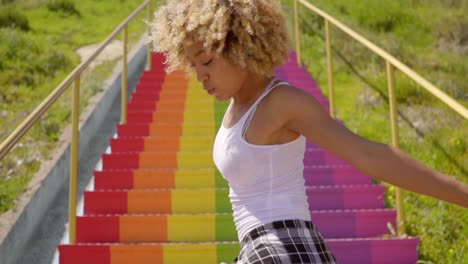 Sexy-young-woman-dancing-on-rainbow-colored-steps
