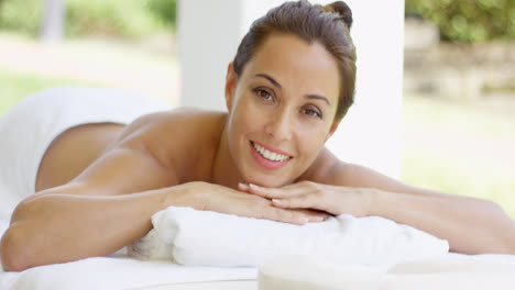 Woman-with-chin-on-folded-towel-smiles