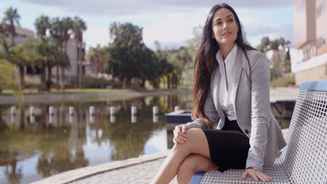 Business-woman-sitting-on-bench-looking-away