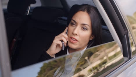 Serious-female-executive-on-phone-in-limousine
