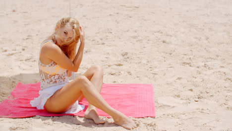 Sensual-Woman-Sitting-on-the-Mat-at-the-Beach