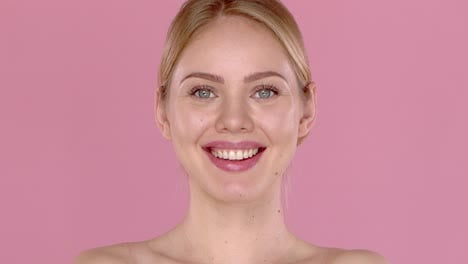 Slow-motion-video-shot-of-smiling-beautiful-girl-isolated-on-pink-background-Bare-shoulders