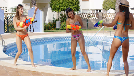 Three-young-women-playing-with-colorful-water-guns