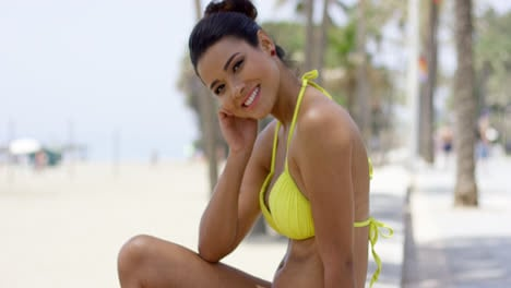Cute-woman-in-yellow-bikini-sitting-on-beach-wall
