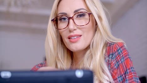 Blond-Woman-with-Glasses-Busy-with-Tablet-Computer