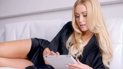Woman-in-Sexy-Silky-Robe-Lying-on-Sofa-with-Tablet