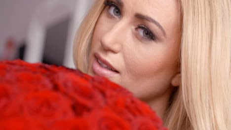 Seductive-Blond-Woman-Behind-Red-Rose-Bouquet
