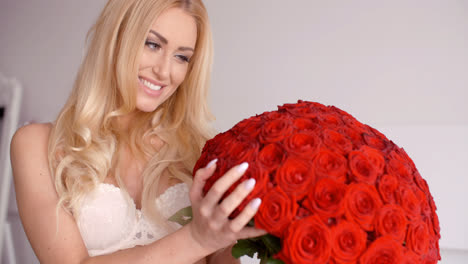 Pretty-Woman-in-White-Bra-Touching-a-Rose-Bouquet