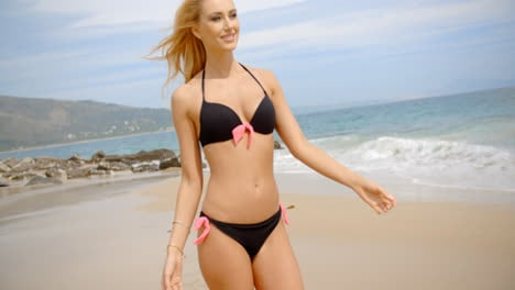Smiling-Blond-Woman-in-Bikini-Walking-on-Beach