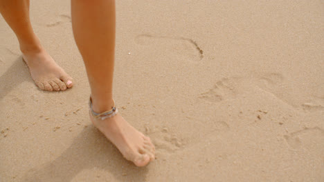 Bare-Feet-Coated-in-Sand-Walking-on-Beach