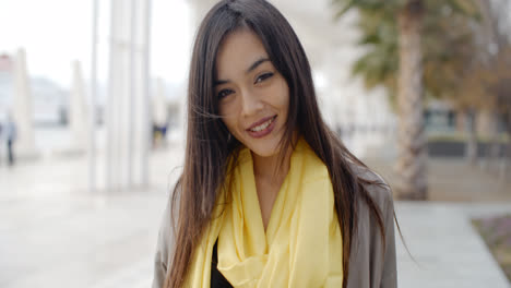 Joyful-grinning-woman-outside-in-yellow-scarf