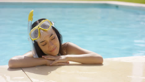 Woman-in-snorkel-and-goggles-rests-by-pool