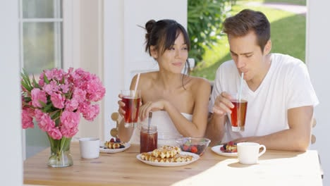 Couple-drinking-iced-tea-at-breakfast-outside