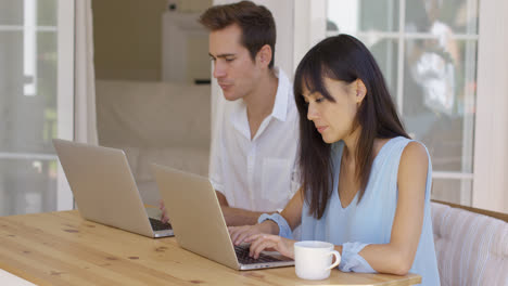Calm-young-couple-sitting-at-table-using-laptop