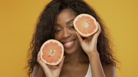 Cheerful-black-lady-showing-halves-of-grapefruit