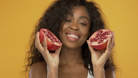 Pleased-black-woman-with-pomegranate