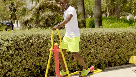 Man-in-park-uses-painted-metal-exercise-equipment