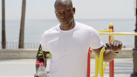 Athlete-with-uncapped-sports-bottle-in-park