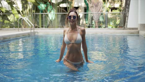 Cheerful-woman-walking-in-swimming-pool