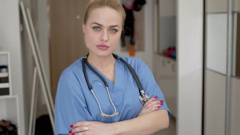 Head-shot-of-female-doctor-wearing-blue-coat-and-stethoscope-on-shoulders-looking-at-camera