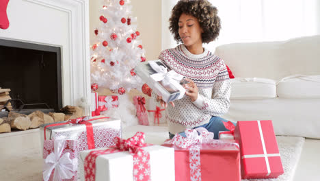 Smiling-young-woman-opening-her-gifts-at-Christmas