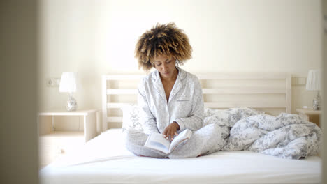 Woman-Reading-A-Book-On-Bed