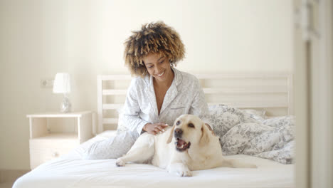 Woman-Is-Holding-A-Dog-On-A-Bed