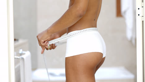 Front-View-Of-Slender-Woman-Measuring-Waist-
