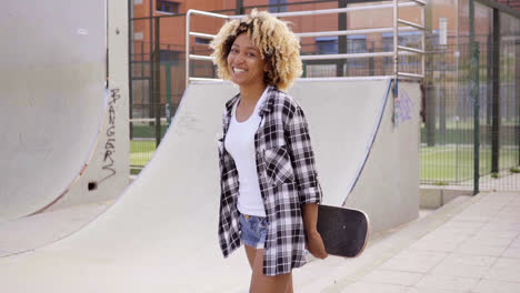 Charismatic-young-woman-holding-a-skateboard