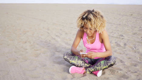 Woman-sitting-at-beach-listening-to-music
