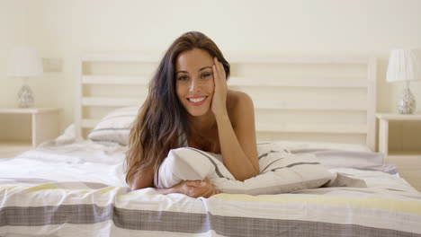 Woman-with-cheerful-expression-laying-down-on-bed
