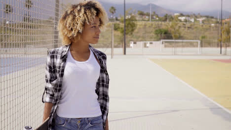 Young-woman-with-skateboard-poses-by-ball-court