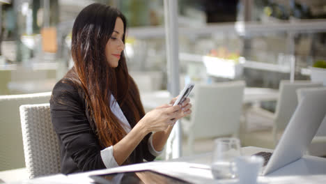 Businesswoman-checking-her-mobile-phone