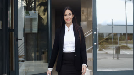 Young-businesswoman-exiting-a-modern-office